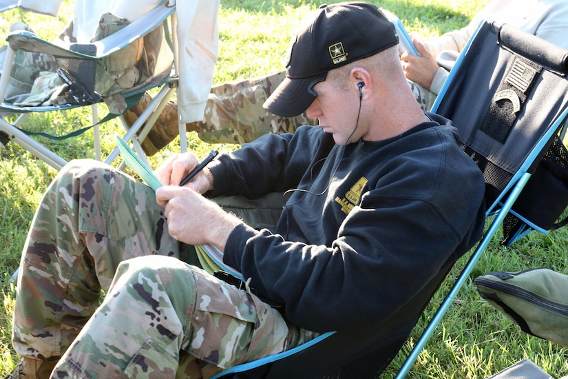 Soldier takes notes during marksmanship competition.