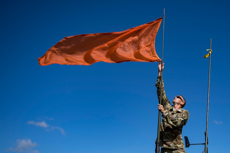 U.S. Air Force Tech. Sgt. John Schmidt, 820th Combat Operations Squadron (COS) NCO in charge of aircrew flight equipment, raises a flag that assists the drop-zone team in recognizing wind direction, Oct. 3, 2017, at the Lee Fulp drop zone in Tifton, Ga. The 820th COS's four-person shop of parachute riggers are responsible for ensuring every 820th Base Defense Group parachute is serviceable, while also ensuring ground safety at the drop zone. The team has packed and inspected more than 490 parachutes in 2017. (U.S. Air Force photo by Airman 1st Class Daniel Snider)