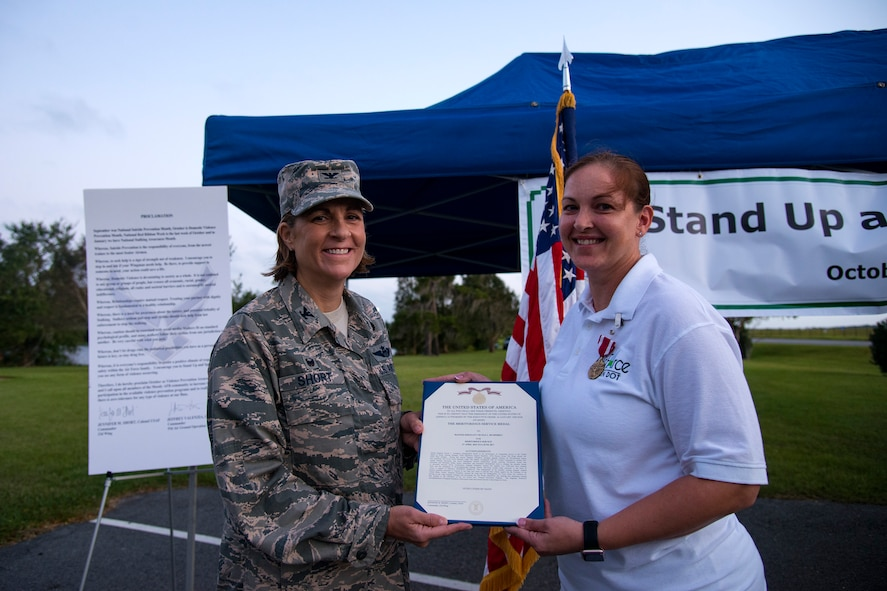 Col. Jennifer Short, 23d Wing commander, left, and Master Sgt. Nicole Humphrey, 23d Maintenance Group training section chief, pose for an award, Oct. 4, 2017, at Moody Air Force Base, Ga. Humphrey received the Meritorious Service Medal for her service with Green Dot, a training program dedicated to violence prevention. (U.S. Air Force photo by Airman 1st Class Erick Requadt)