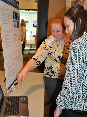 "IMAGE: DAHLGREN, Va. (Sept. 29) - NSWC Dahlgren Division computer scientist Teeya Roche and software lead Megan Kozub explain ""Data Visualization Support for Creation of a Numerical Table: Effects on Training and Performance"" at the In-House Laboratory Independent Research and Independent Applied Research review. The study was designed to test principles of data visualization to decrease the information processing assessment time for decision-making; increase understanding of visual-based doctrine, and reduce incorrect doctrine creation."