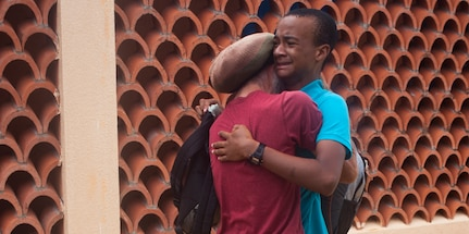 U.S. citizen David Shargel embraces his son, Naya Shargel, at Douglas-Charles Airport in Melville Hall, Dominica