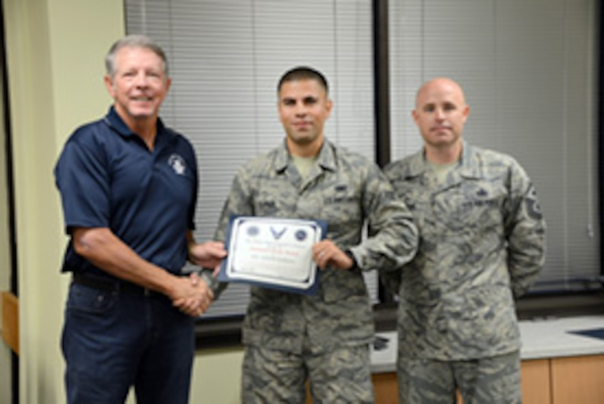 Airman 1st Class Adam Khrais, with the 552nd Maintenance Group, is presented his Diamond Sharp Award by the 15th Chief Master Sgt. of the Air Force Rodney McKinley and his first sergeant, Master Sgt. Paul Barentine.