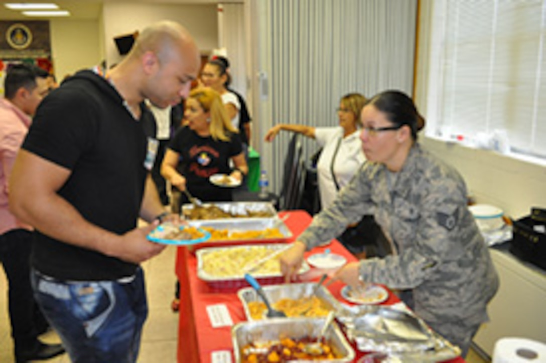 Staff Sgt. Cheila with the 960th Airborne Air Control Squadron gets ready to serve a Puerto Rican dish to Senior Airman Daniel with the 966th AACS on Sept. 21.