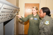Staff Sgt. Victoria Thompson, left, an instructor with the 966th Airborne Air Control Squadron, explains the various functions of the P66-1 circuit breaker panel to Airman 1st Class Hannah Jean-Marie from the 552nd Training Squadron.