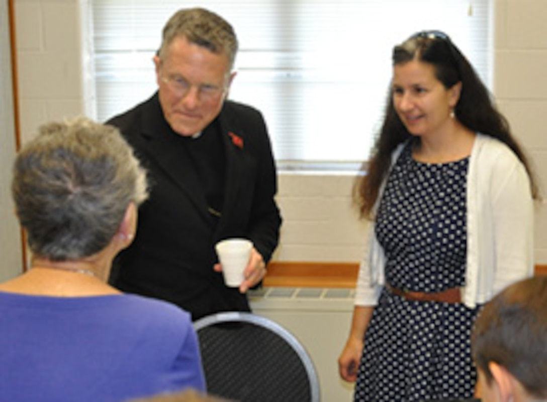 Archbishop Timothy Broglio, head of the Catholic Archdiocese for the Military Services, speaks to a Tinker Chapel parishioner Sept. 24 as Lt. Col. Heather Fleishauer, commander of the 752nd Operations Support Squadron, listens in.