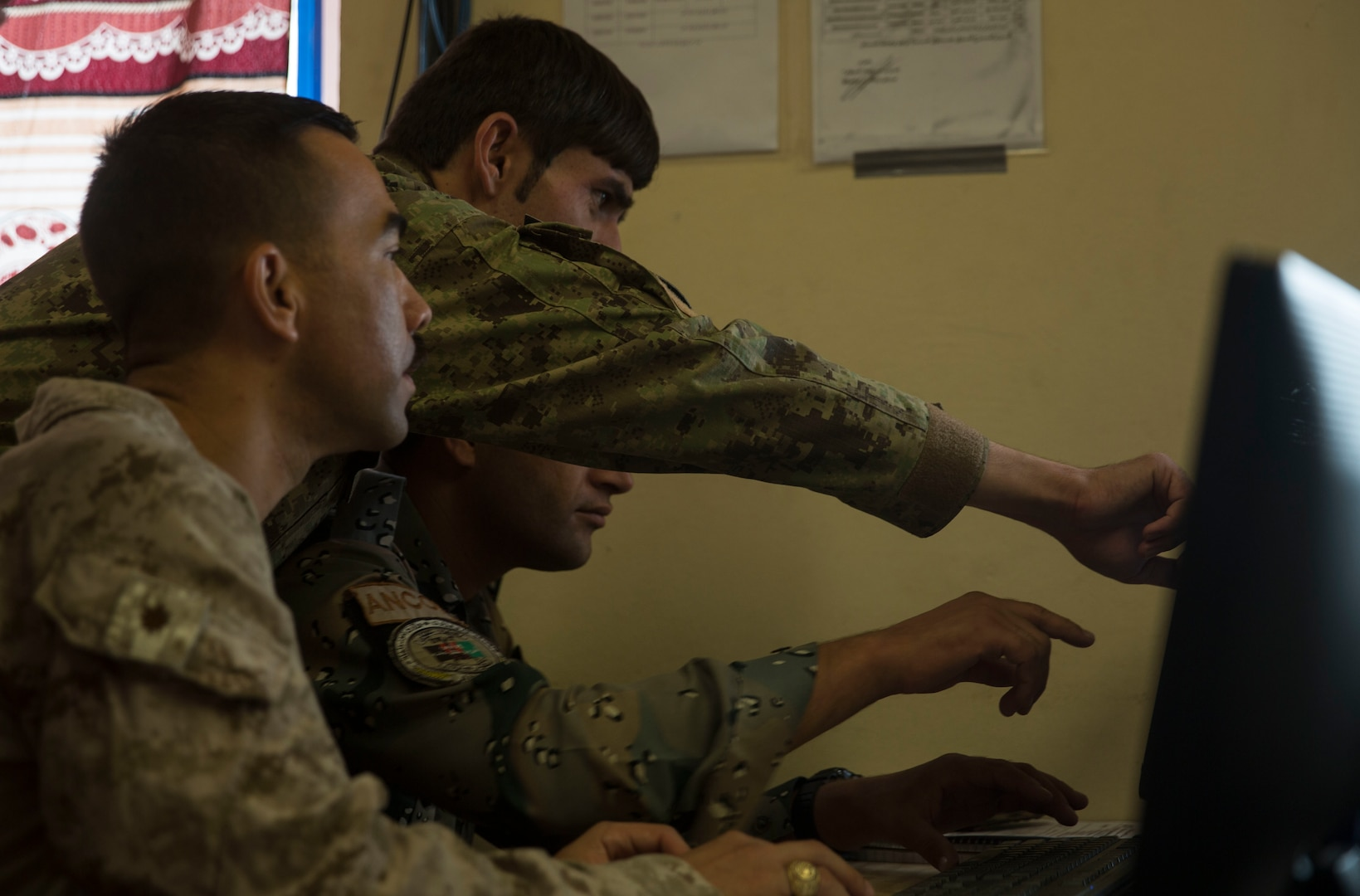 A U.S. Marine advisor with Task Force Southwest and Afghan National Defense and Security Force policemen work through an issue at the Operational Coordination Center – Regional at Bost Airfield, Afghanistan, Oct. 2, 2017. One of the primary missions of the OCC-R is to maintain situational awareness with operational forces on the ground and provide information to ground commanders so they can manage their forces and resources effectively. (U.S. Marine Corps photo by Sgt. Justin T. Updegraff)