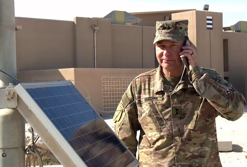 Major General Edward Dorman, director for logistics, U.S. Central Command, charges a hand-held portable device from a USB port powered by a solar powered light cart at Camp Arifjan, Kuwait. The carts are part of an operational energy initiative to reduce USCENTCOM's carbon footprint and reliance on fossil fuels. (379th Air Expeditionary Wing Public Affairs courtesy image)