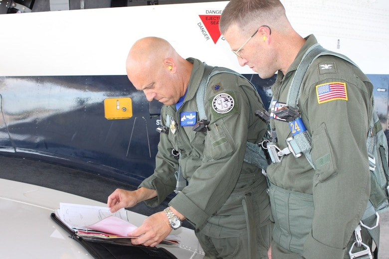 Lt. Col. Andrew Kissinger and U.S. Coast Guard Capt. Tony Hahn review their checklists before flying the T-6 Texan II. The USCG Corpus Christi sector commander/air station commanding officer reached out to the 39th Flying Training Squadron to discuss pilot retention/recruiting and reserve integration benefits. Closing out his visit, Kissinger took him on a familiarization flight. (Photo by Debbie Gildea, 340th Flying Training Group Public Affairs).