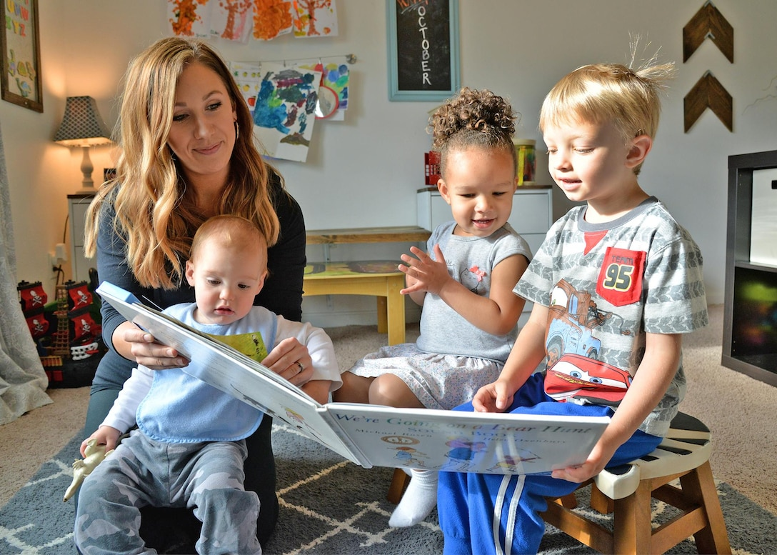 Family Child Care provider Emily Horn reads to (left to right) Alden Von Thaden, Kendall Finley and Benjamin Brown Oct. 5 during playtime at her on-base, FCC home.