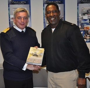 "IMAGE: DAHLGREN, Va. (Oct. 2, 2017) - British Royal Navy First Sea Lord Adm. Sir Philip Jones holds the Dahlgren history book, ""The Sound of Freedom,"" he just received from Capt. Godfrey ""Gus"" Weekes, Naval Surface Warfare Center Dahlgren Division (NSWCDD) commanding officer, as the two shake hands. The 1SL and his delegation toured NSWCDD laboratories and test sites for overviews on programs ranging from human systems integration and ballistic missile fire control to directed energy weapons, including the electromagnetic railgun and high energy lasers."