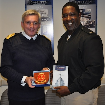 "IMAGE: DAHLGREN, Va. (Oct. 2, 2017) - British Royal Navy First Sea Lord Adm. Sir Philip Jones presents a book on the Royal Navy and a plaque to Capt. Godfrey ""Gus"" Weekes, Naval Surface Warfare Center Dahlgren Division (NSWCDD) commanding officer, during his tour of NSWCDD. The 1SL and his delegation toured NSWCDD laboratories and test sites for overviews on programs ranging from human systems integration and ballistic missile fire control to directed energy weapons, including the electromagnetic railgun and high energy lasers. The command provides research, development, test and evaluation, analysis, systems engineering, integration and certification of complex naval warfare systems."