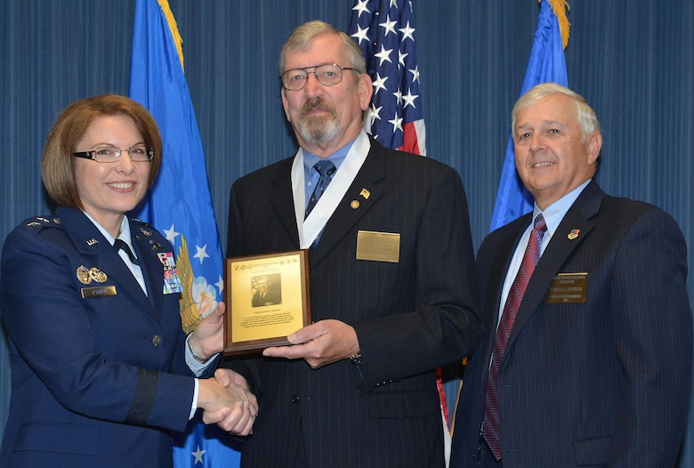 Retired Chief Master Sgt. Kenneth C. Maynard receives his Hall of Honor plaque from Maj. Gen. Mary O'Brien, commander, 25th Air Force, and retired Col. Ronald Haygood, president, Freedom Through Vigilance Association.