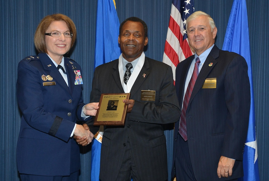 Retired Chief Master Sgt. Jesse L. Greene receives his Hall of Honor plaque from Maj. Gen. Mary O'Brien, commander, 25th Air Force, and retired Col. Ronald Haygood, president, Freedom Through Vigilance Association.