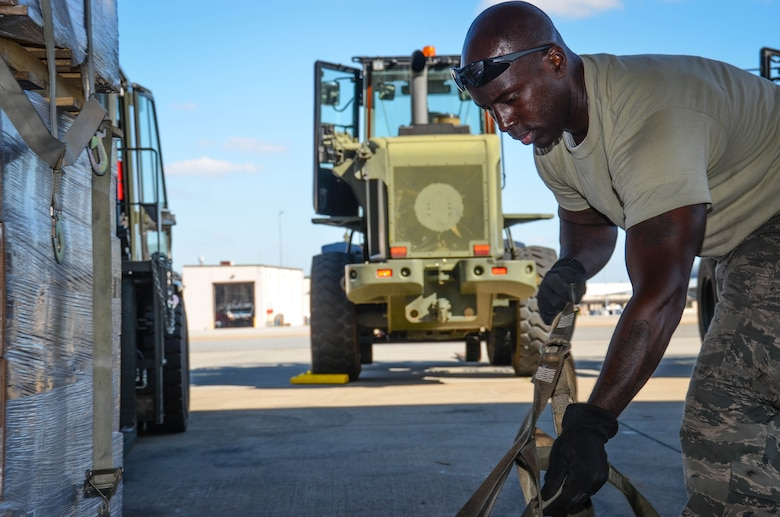 Staff Sgt. Kens Germain, an aerial porter from Joint Base McGuire-Dix-Lakehurst, New Jersey, straps down a stack of meals ready-to-eat at Dobbins Air Reserve Base, Ga., on Oct. 4. A total of 23,390 pounds of food and water will be transported to Puerto Rico and distributed to those in need. (U.S. Air Force photo by Tech. Sgt. Kelly Goonan)