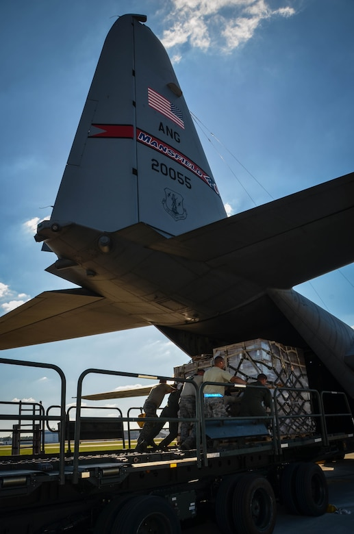 Airmen position a K-loader carrying water and ready-to-eat meals behind a C-130 Hercules at Dobbins Air Reserve Base, Ga. Oct. 4. Airmen loaded a Mansfield Air National Guard C-130 with a total of 23,390 pounds of food and water which will be transported to Puerto Rico and distributed to those in need. (U.S. Air Force photo by Tech. Sgt. Kelly Goonan)