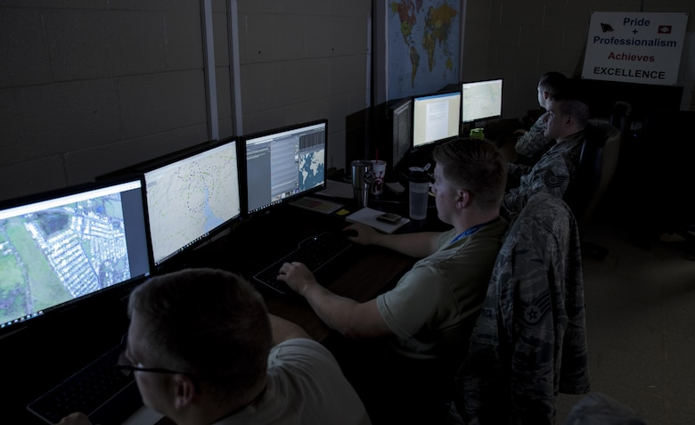 "Four Airmen sit in a dark room looking at computer monitors that have over head imagery of locations in Puerto Rico. There is a sign in the background that reads ""Pride + Professionalism achieves excellence""."
