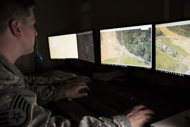 In a dark room, Staff Sgt. Danny sits at a desk looking at two computer screens that have over head images of the Guajataca dam.  You can see the erosion of the dam in the images.