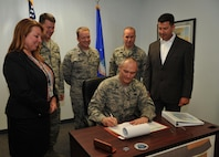 Master Sgt. Martin Vessels, 9th Contracting Squadron construction flight chief, signs a contract regarding upcoming renovations to the pool in base housing