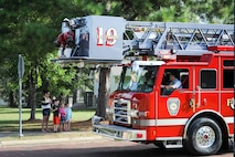 """A family in Magnolia Village on Columbus Air Force Base, Mississippi, waves to a fire truck from the City of Columbus Fire and Rescue Sept. 30, 2017, as part of a parade for Fire Prevention Week. Members of the Columbus AFB Fire Department planned a week full of fire prevention events from Sept. 25-30, and this year's theme was """"Every Second Counts: Plan 2 Ways Out!"""" (U.S. Air Force photo by Staff Sgt. Christopher Gross)"""