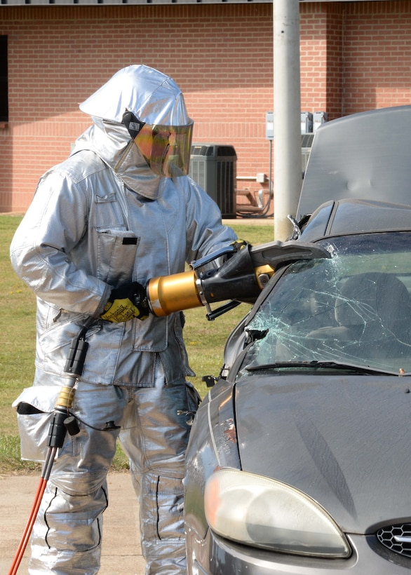 Senior Airman Ryan Offerman, 14th Civil Engineer Squadron firefighter, uses a power tool to cut up a vehicle for a live rescue demonstration Sept. 30, 2017, on Columbus Air Force Base, Mississippi. The demonstration simulated an accident that involved texting while driving and showed how the firefighters have to rescue the victim. The event was part of Fire Prevention Week Sept. 25-30. (U.S. Air Force photo by Airman 1st Class Beaux Hebert)