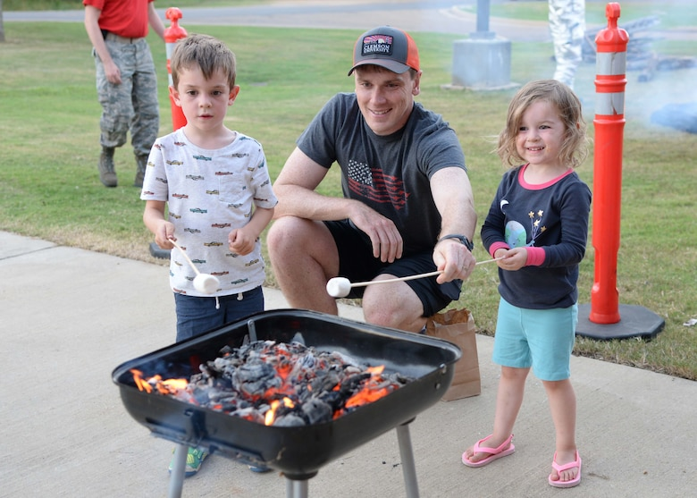 Capt. Zachary Shuler, 14th Operations Group Standards and Evaluation, and his two children, Grady and Paige, roast marshmallows Sept. 29, 2017, on Columbus Air Force Base, Mississippi. The Columbus Fire Department hosted multiple family activities in honor of Fire Prevention Week Sept. 25-30. (U.S. Air Force photo by Airman 1st Class Beaux Hebert)