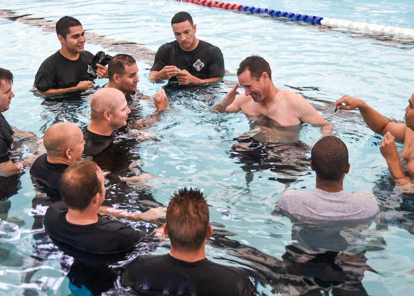 Col. Richard Reed, 377th Force Support Squadron commander, coins all instructors from the 58th Operations Support Squadron in the pool after training.  Airmen from the 377th Force Support Squadron and 150th Special Operations Wing completed an overturned-aircraft simulation, compressed-air breathing exercises and various parachute escape exercises.