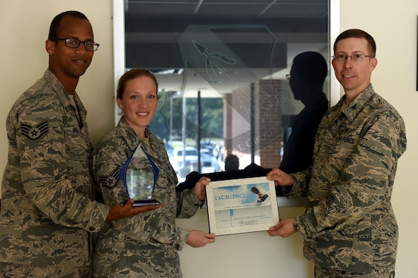 Staff Sgt. Johnmarth Perez (left), 4th Medical Support Squadron laboratory service NCO in charge, and Staff Sgt. Erin Holmquist (middle), 4th MDSS medical laboratory floor supervisor, are presented the 2017 Air Force Medical Services Customer Service award by Col. Craig Keyes (right), 4th Medical Group commander, Oct. 4, 2017, at Seymour Johnson Air Force Base, North Carolina. This is the second year the staff sergeants have created videos that have won through this contest. (U.S. Air Force photo by Airman 1st Class Miranda A. Loera)