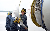 U.S. Navy Strategic Communications Wing ONE Detachment Sailors Airman Alfredo Valdez, Airman Benaiah Hague, and Petty Officer Petty Officer Third Class Jurgen Baezabernal open the engine cowling to service oil during a turn-around inspection on an E-6 Mercury here Oct. 3.