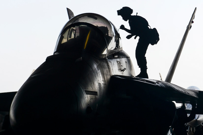 A sailor, shown in silhouette, stands on an aircraft wing and performs maintenance.