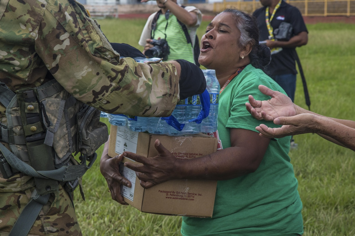 A soldier hands water and food to a woman.