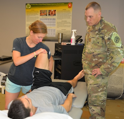 1st Lt. Veronica Lazar (left), Army-Baylor University Doctor of Physical Therapy program intern, practices a physical therapy technique on 1st Lt. Aaron Wilson, Army-Baylor University Doctor of Physical Therapy program intern, while taking instructions from Maj. Justin Zimmerman, student clinician in the Army-Baylor University Doctoral Fellowship in Orthopaedic Manual Physical Therapy program, as part of a research project at the Capt. Jennifer M. Moreno Primary Clinic at Joint Base San Antonio-Fort Sam Houston.