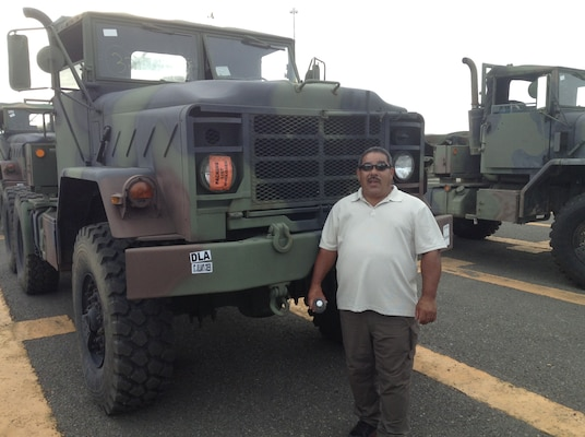A man stands in a parking lot next to a truck nearly twice as tall as he is
