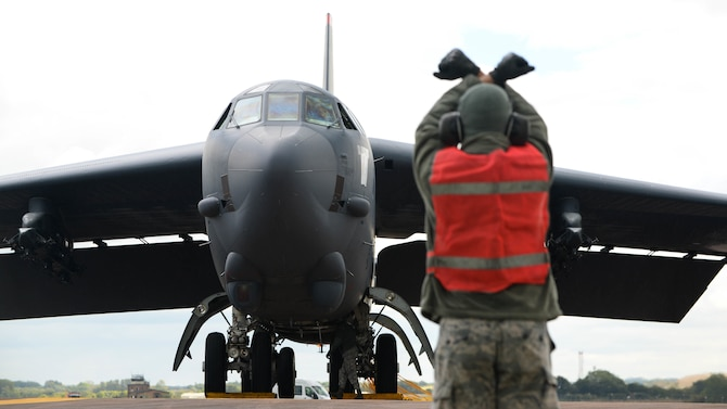 A B-52 Stratofortress is marshalled to a parking spot at Fairford Royal Air Force Base, U.K., Sept. 14, 2017.