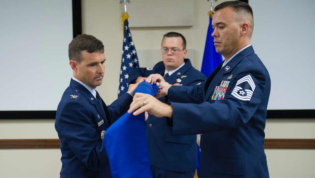 The 45th Space Wing Operations Group commander, Colonel Burton Catledge, assisted by Chief Master Sergeant Alec Hall, retires the Range Management Squadron flag at the inactivation ceremony on Friday, 6 October, 2017.