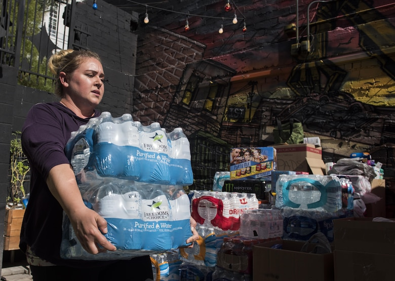 Shannon Janelle, mother of two and wife of Staff Sgt. Jeffrey Janelle, an instructor assigned to the Nellis First Term Airman Center, carries water to a donation site in downtown Las Vegas, Oct. 5, 2017. Shannon teamed with more than 30 spouses, friends and families to collect donated items for those at Sunrise Hospital, the University Medical Center of Southern Nevada, the Las Vegas Convention Center and the Las Vegas fire and police departments. (U.S. Air Force photo by Senior Airman Kevin Tanenbaum/Released)