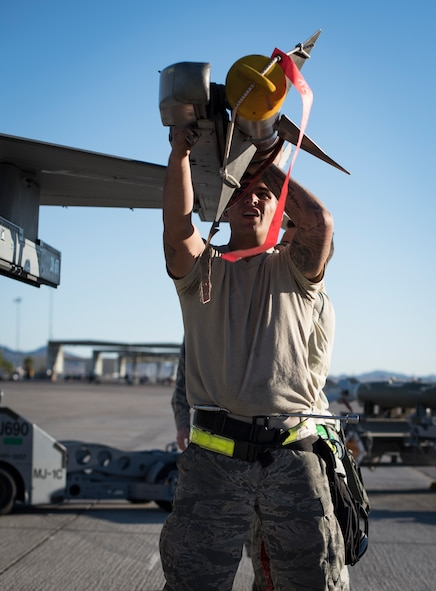 Airmen from the 57th Maintenance Group arm an F-16 Fighting Falcon during a load crew competition at Nellis Air Force Base, Nev., Oct. 6, 2017. Small teams worked together to load multiple large munitions on the aircraft. (U.S. Air Force photo by Airman 1st Class Andrew D. Sarver/Released)