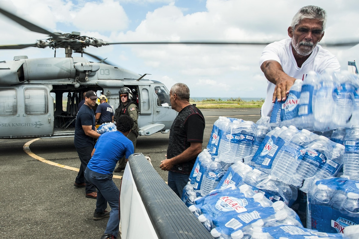 Sailors and others unload relief supplies from a helicopter.