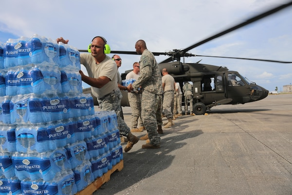 U.S. Soldiers, assigned to 42nd Combat Aviation Brigade, 3-142nd Assault Helicopter Battalion, load bottled water onto a UH-60 Black Hawk helicopter, San Juan, Puerto Rico, Oct. 5, 2017. The 3-142nd Assault Helicopter Battalion support the Hurricane Maria Relief by supplying water, food, and supplies to locals throughout several different locations devastated by the hurricane. (U.S. Army photo by Pfc. Caitlyn Cassidy)