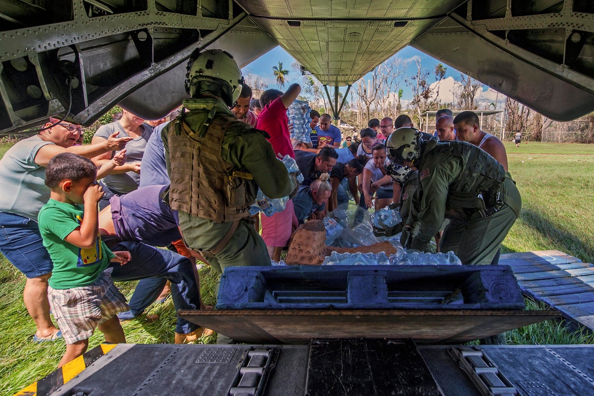 A group of people pick up water and other supplies behind an aircraft.