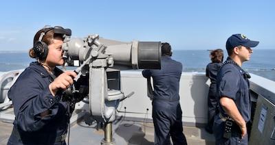 Sailor looks through binoculars.