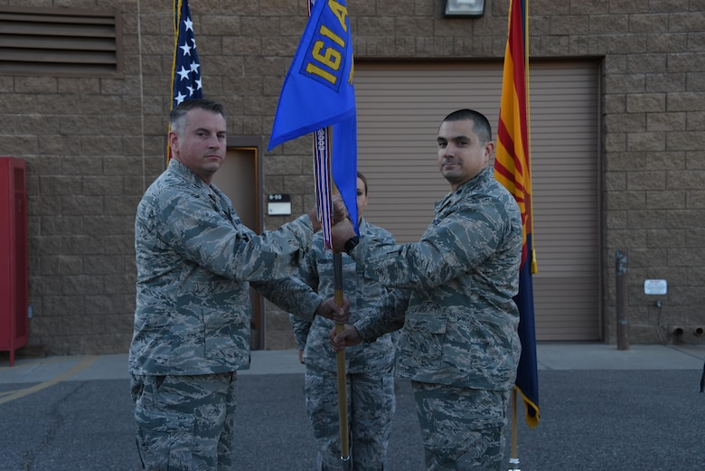 Col. David Ciesielski, 161st Air Refueling Wing Mission Support Group commander, passes the guidon to Lt. Col. Vince Navarro as he assumes command of the 161st Security Force Squadron, Oct. 7. (U.S. Air National Guard photo by 2nd Lt. Tinashe Machona).