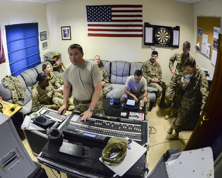 Members of the U.S. Air Force Central Command Band, Touch-n-Go, gathered behind U.S. Air Force Tech. Sgt. John Marsh, foreground, audio engineer, as they listen to a recording they recently cut of the Air Force Song at Al Udeid, Air Force Base, Qatar, Sept. 21, 2017.