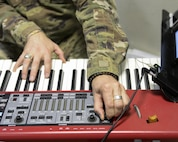 U.S. Air Force Staff Sgt. Robert Barnes, keyboardist assigned to the Air Force Central Command Band, Touch-n-Go, plays keyboard during a recording session as the band recorded their punk rock rendition of the Air Force Song at Al Udeid, Air Force Base, Qatar, Sept. 21, 2017.