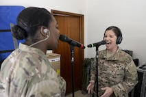 U.S. Air Force Staff Sgt. Melissa Lackore, right, and Senior Airman Paula Hunt, vocalists assigned to the Air Force Central Command Band, Touch-n-Go, sing the Air Force Song during a recording session at Al Udeid, Air Force Base, Qatar, Sept. 21, 2017.