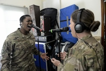 U.S. Air Force Senior Airman Paula Hunt, left, and Staff Sgt. Melissa Lackore, vocalists assigned to the Air Force Central Command Band, Touch-n-Go, sing the Air Force Song during a recording session at Al Udeid, Air Force Base, Qatar, Sept. 21, 2017.