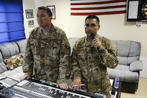 U.S. Air Force Capt. Rafael Toro-Quinones, right, officer in charge, communicates with band members recording in another building while Tech. Sgt. John Marsh, audio engineer, both assigned to the Air Force Central Command Band, Touch-n-Go, assists with the production during a recording session as the band recorded their punk rock rendition of the Air Force Song at Al Udeid, Air Force Base, Qatar, Sept. 21, 2017.