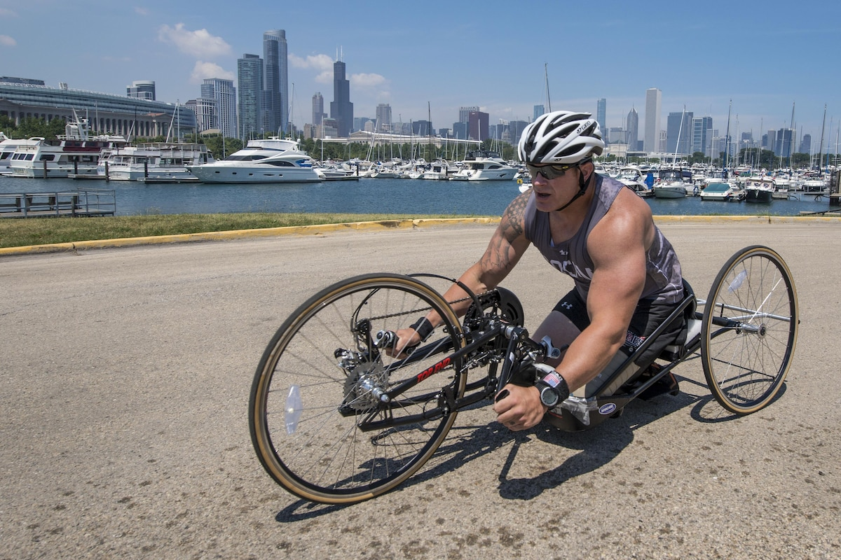 A cyclist competes in an event with the Chicago skyline behind him.