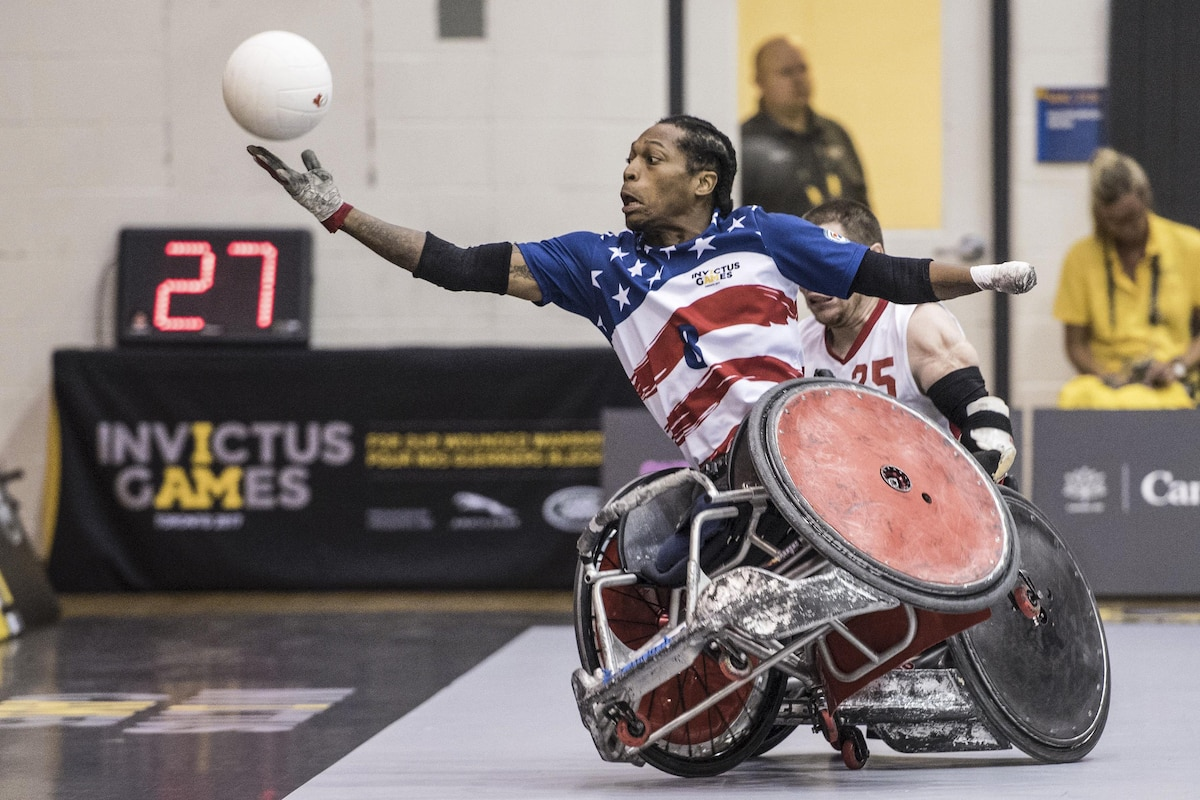 A Marine Corps veteran reaches for a ball during a wheelchair rugby game.