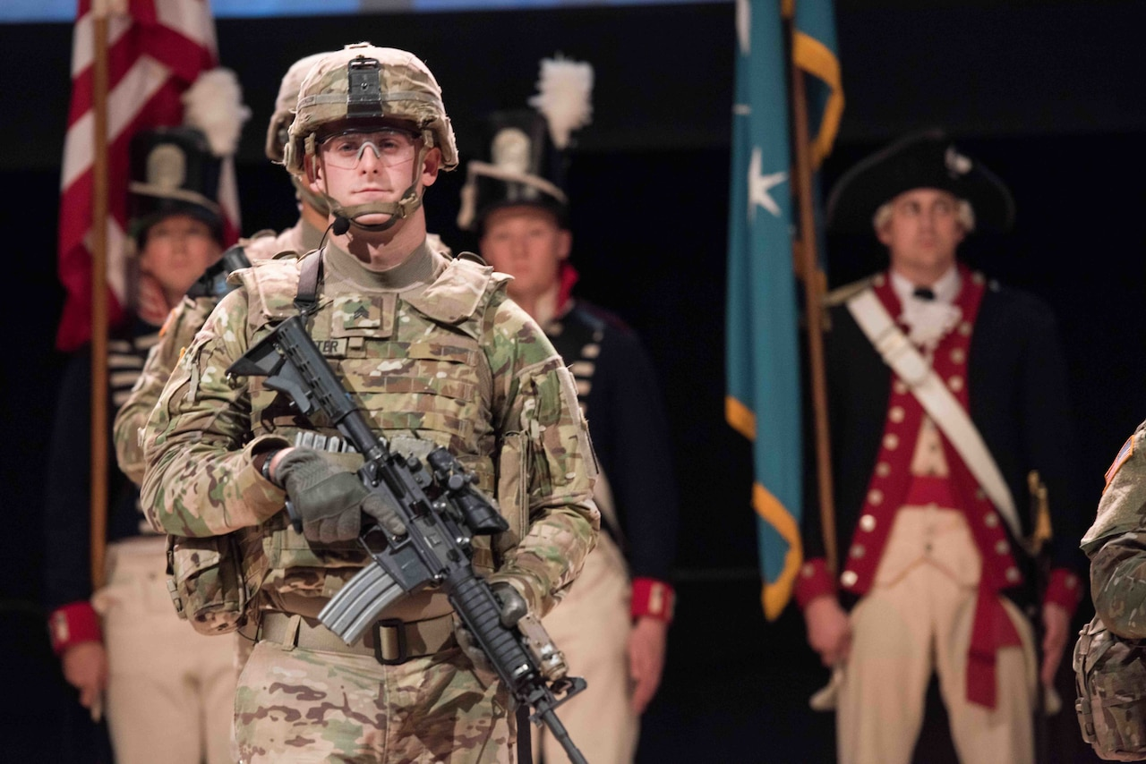 Soldier in battle gear participates in ceremony to open conference.
