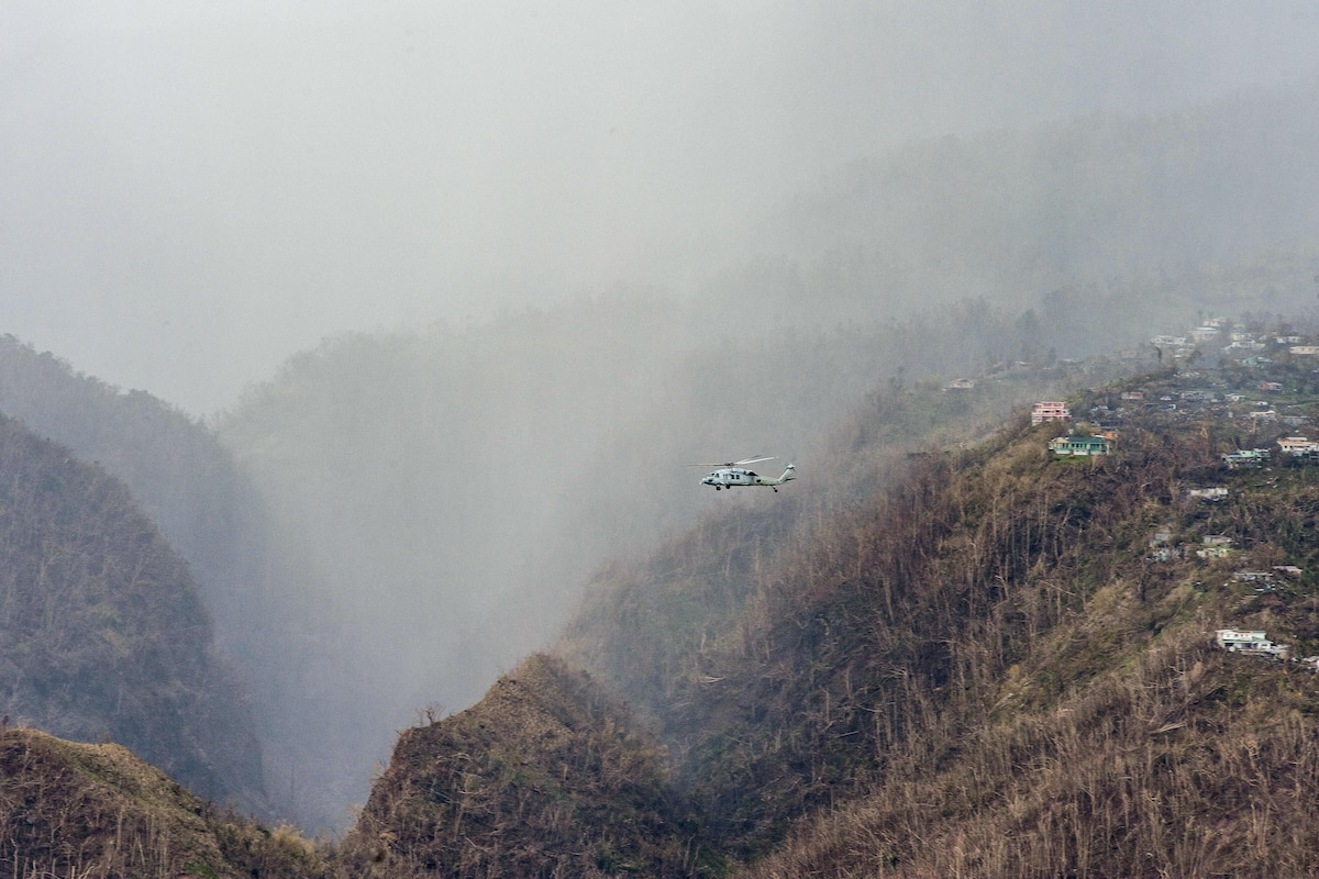 A helicopter evacuates residents from a mountain community.